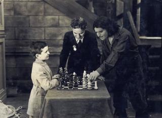 Samuel Reshevsky con Charlie Chaplin y Douglas Fairbanks juegando ajedrez durante el rodaje de la película Los tres mosqueteros en 1921.